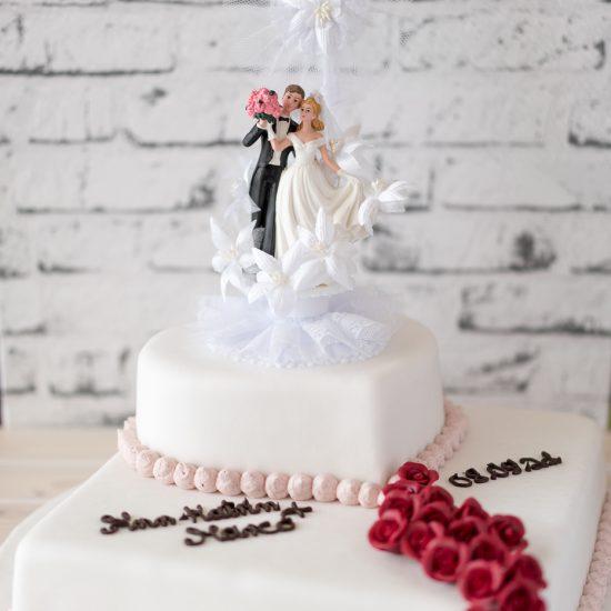 Hochzeitstorte aus Buttercreme zweistöckig (eckig & herzförmig), mit Brautpaar, Namenszug, Datum & kleiner Rosenranke