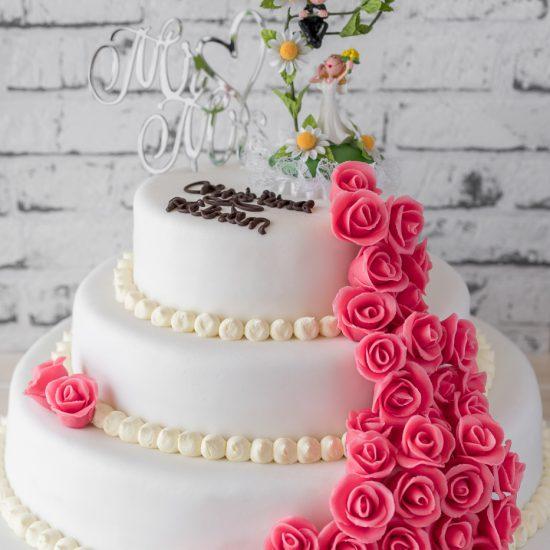 Hochzeitstorte aus Buttercreme dreistöckig mit Brautpaar, Topper, Namenszug & Rosenranke