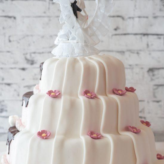 Hochzeitstorte halb offen aus Buttercreme dreistöckig mit Brautpaar
