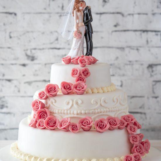 Hochzeitstorte aus Buttercreme dreistöckig mit Randgarnitur, Brautpaar und Rosenranke