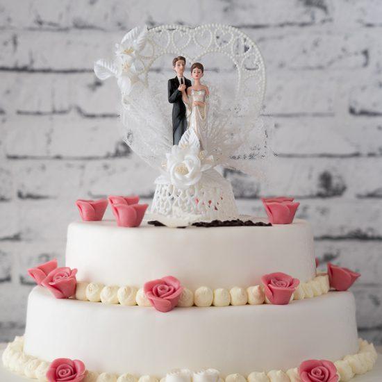 Hochzeitstorte aus Buttercreme zweistöckig mit Brautpaar, Namenszug und einzelnen Rosen